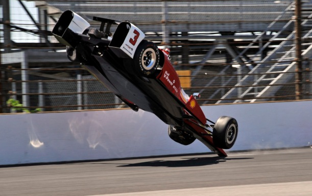 The car driven by Helio Castroneves, of Brazil, flips after hitting the wall in the first turn during practice for the Indianapolis 500 auto race at Indianapolis Motor Speedway in Indianapolis, Wednesday, May 13, 2015.  (AP Photo/Dick Darlington) ORG XMIT: NAA110